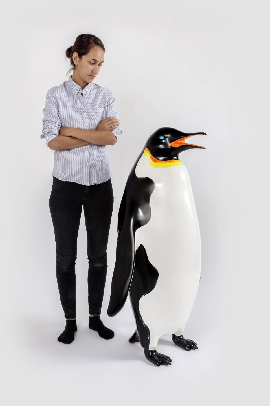 Penguin sculpture next to human