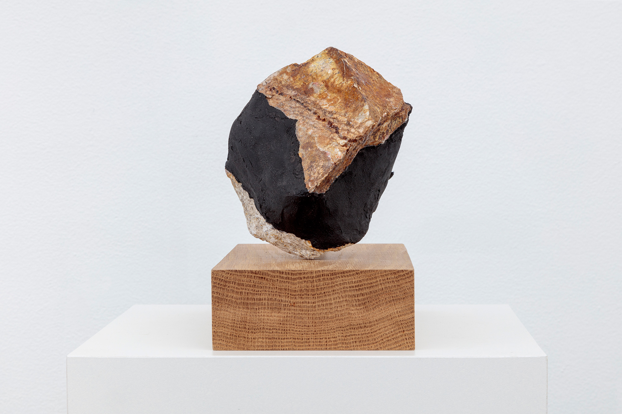 Sculpture with rock on wooden pedestal