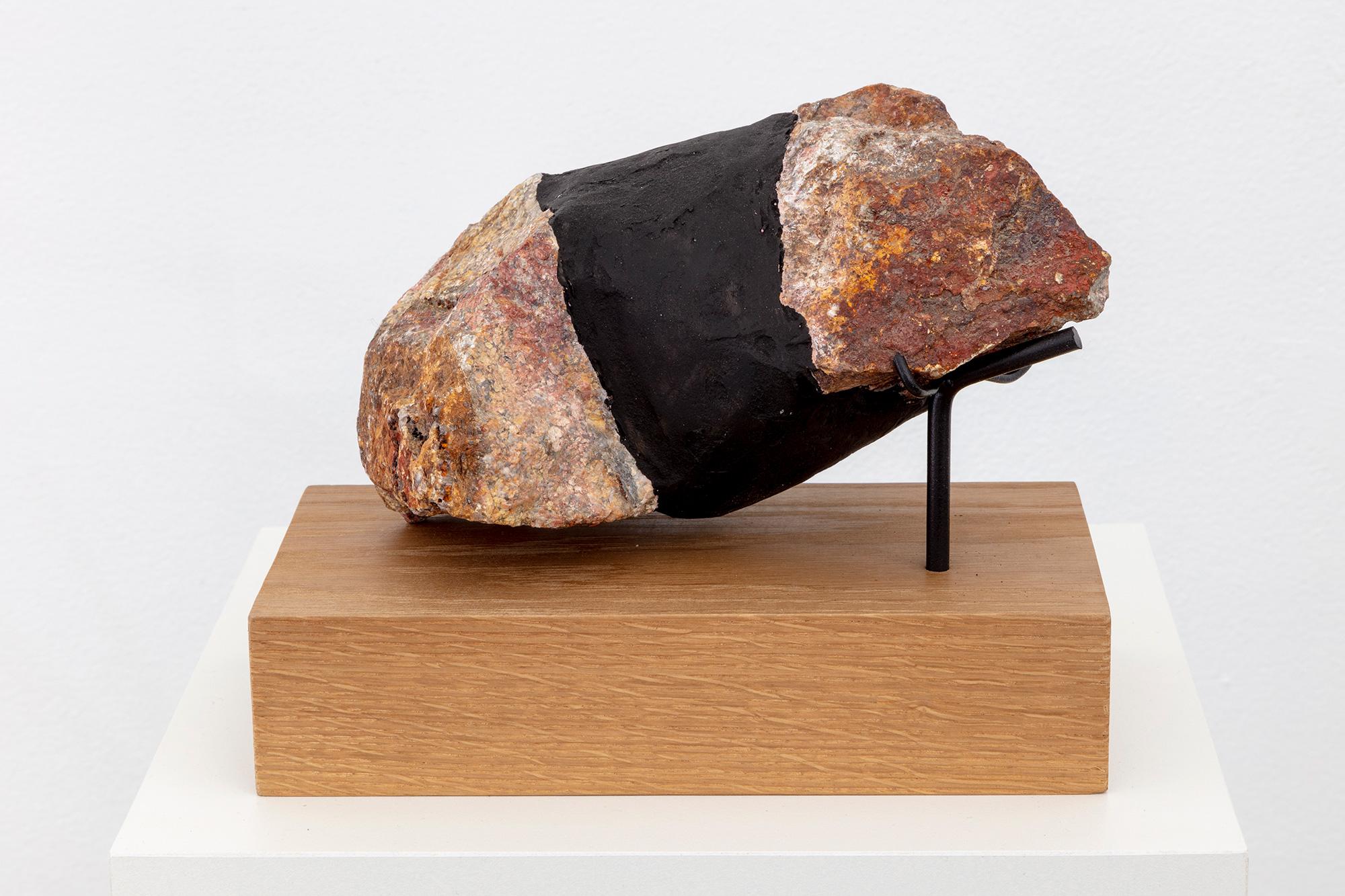 Sculpture with rock on wooden pedestal