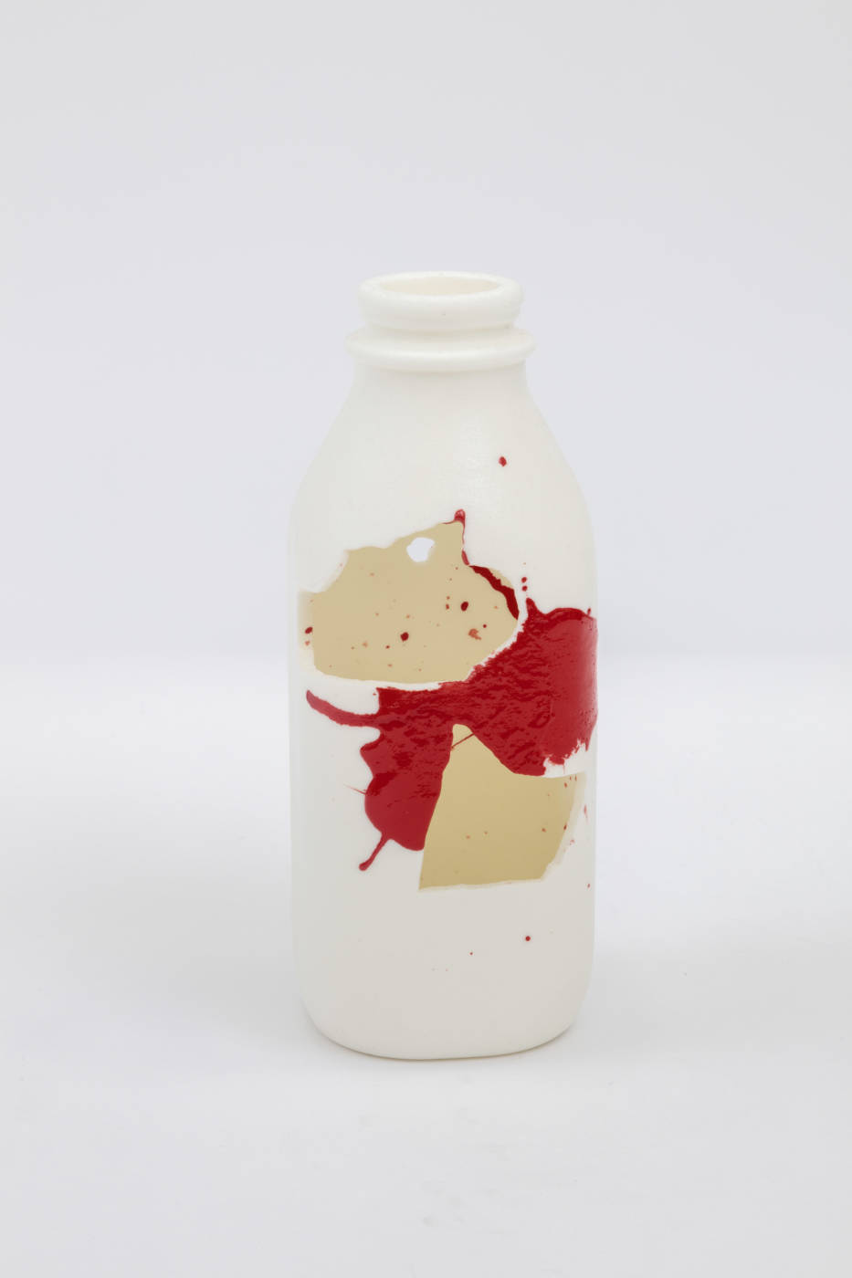Bottle sculpture with splashes of cream and red color