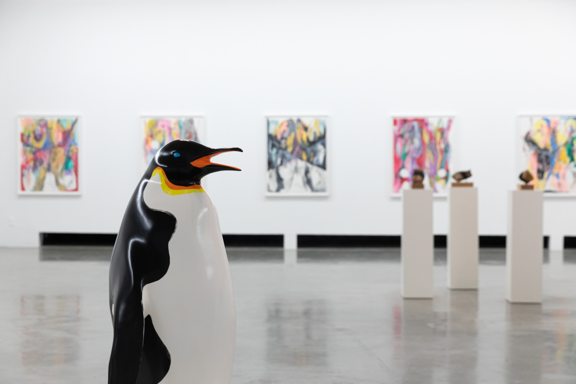 Artworks in gallery, penguin sculptures in front